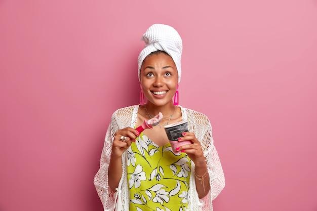 Positieve etnische huisvrouw draagt casual huiskleding gewikkeld handdoek op hoofd eet lekker koud ijs met lepel kijkt erboven glimlacht tandachtig geniet van koud zomerdessert geïsoleerd over roze muur