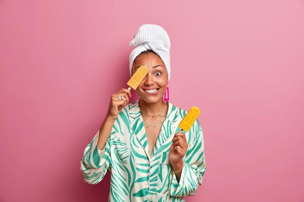 Positieve etnische huisvrouw met donkere huid bedekt oog met lekker koud ijs heeft plezier terwijl het eten van een heerlijk zoet dessert huishoudelijke kleding draagt gewikkeld in een badhanddoek op het hoofd. zomertijd concept