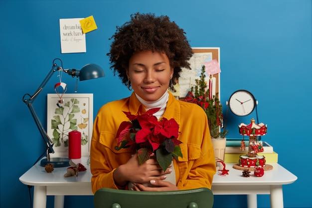 Positieve etnische meisje geniet van plezier om thuis te zijn, vaas met mooie rode bloem omhelst, gele spijkerjasje draagt, vormt op bureaublad en gezellig ingericht interieur