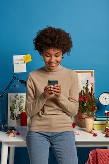 Positieve etnische vrouw blogger leest opmerkingen in blog, geniet van online communicatie, gebruikt moderne mobiele telefoons, staat in coworking space, draagt coltrui en spijkerbroek, bekijkt video in sociale netwerken