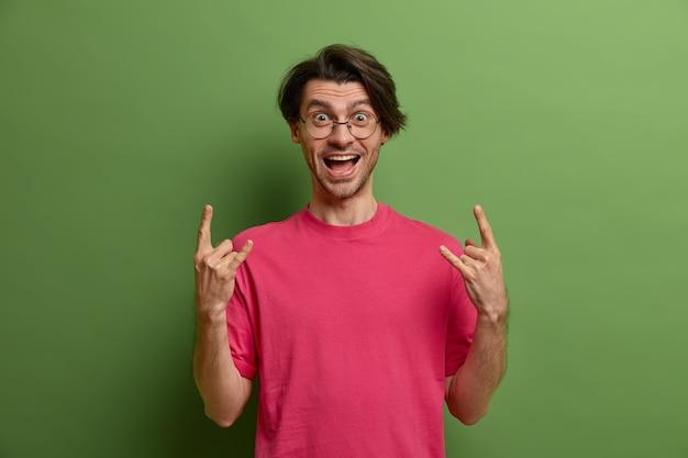 Positieve europese man feesten, geniet van rockmuziek, maakt hoorngebaar, brengt positieve vibes heeft gelukkige uitdrukking draagt karmozijnrode t-shirt, poses