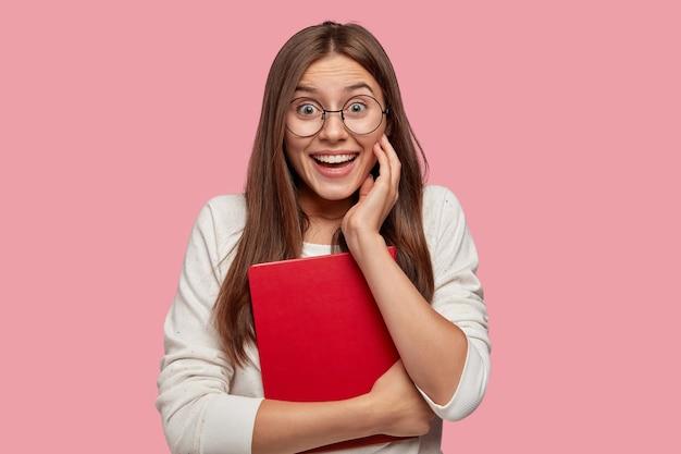 Positieve europese vrouw met steil haar, heeft brede glimlach, giechelt en heeft plezier met klasgenoten, draagt een ronde bril, houdt een rood leerboek vast, verheugt zich met het ontvangen van een goed cijfer, modellen over roze muur
