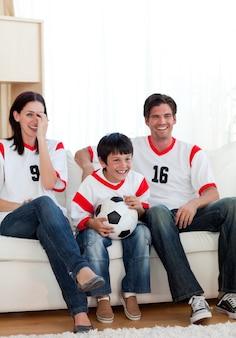 Positieve familie die op voetbalwedstrijd letten