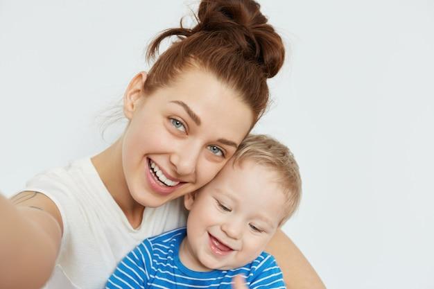 Positieve familie selfie met jonge mama en tandeloze jongen die samen glimlachen op witte muur. de speelse gemoedstoestand en de vrolijke stemming van een aantrekkelijke vrouw maken dit shot fantastisch, hartverwarmend.