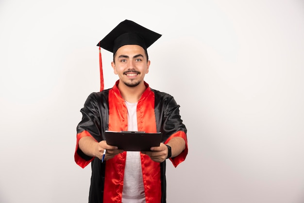 Positieve gediplomeerde student die diploma op wit toont.