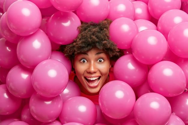 Positieve gekke donkere vrouw ziet er gelukkig uit, wordt verrast, heeft plezier tijdens feestelijke dagen, omringd door kleine opgeblazen roze ballonnen.