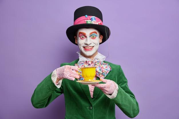 Positieve gekke hoedenmaker draagt heldere kleurrijke make-up geniet van het drinken van thee op feestje gekleed in kostuum viert halloween poses gelukkig tegen paarse muur