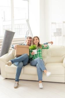 Positieve gekke vrolijke paar verheugt zich in het verhuizen van hun nieuwe appartement zittend in de woonkamer met hun bezittingen. concept van housewarming en hypotheken voor een jong gezin