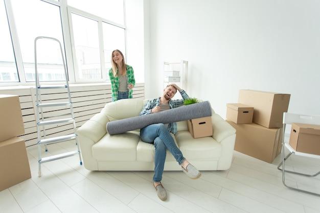 Positieve gekke vrolijke paar verheugt zich in het verhuizen van hun nieuwe appartement zittend in de woonkamer