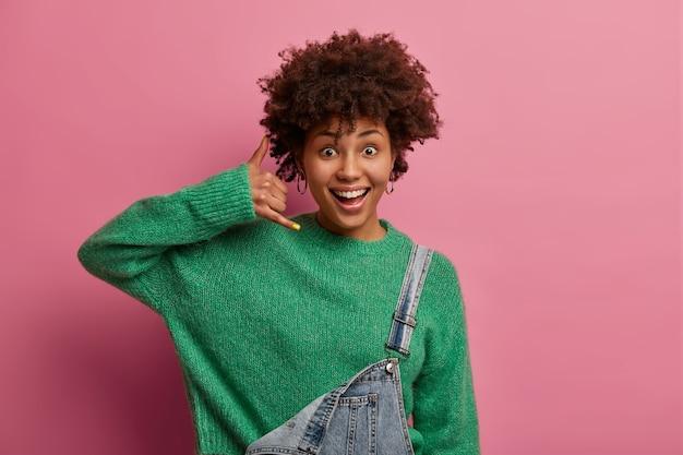 Positieve gekrulde afro-amerikaanse vrouw maakt telefoongebaar, zegt bel me nog een keer, heeft een blije uitdrukking, draagt een groene trui, poseert binnen tegen een roze muur, staat in contact met vrienden