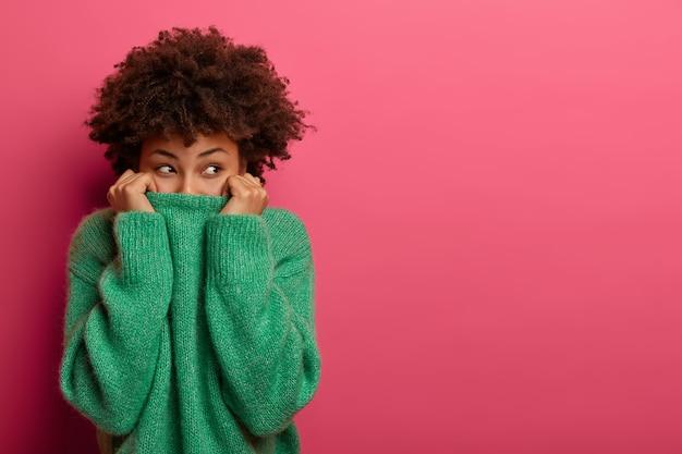 Positieve gekrulde jonge vrouw trekt groene trui over het hoofd, heeft plezier en verbergt gezicht, kijkt van onderaf, verdwijnt in haar kleren, staart vrolijk, geïsoleerd op roze muur, kopieer ruimte