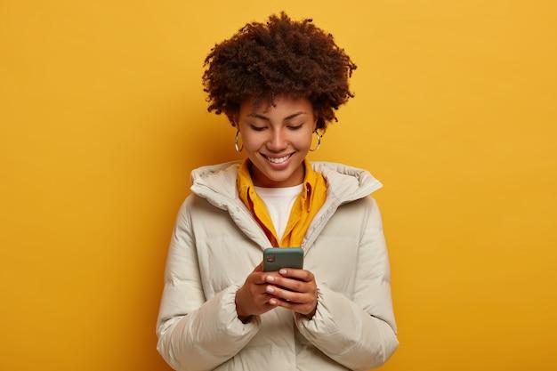 Positieve gekrulde vrouw met behulp van smartphone