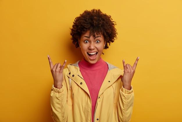 Positieve gekrulde vrouw-vibes op geweldig concert, geniet van feest, maakt rock op gebaar, heavy metal-bord, fan van rocknummers, gekleed in jas, geïsoleerd op gele muur, voelt zich zorgeloos