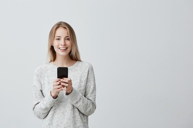 Positieve gelukkig blonde vrouw met brede glimlach met behulp van mobiele telefoon, blij om bericht met goed nieuws te ontvangen, nieuwsfeed op haar sociale netwerkaccounts te controleren. moderne technologieën en communicatie