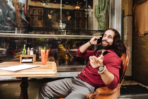 Positieve gelukkig man praten met zijn vriend tijdens het bellen