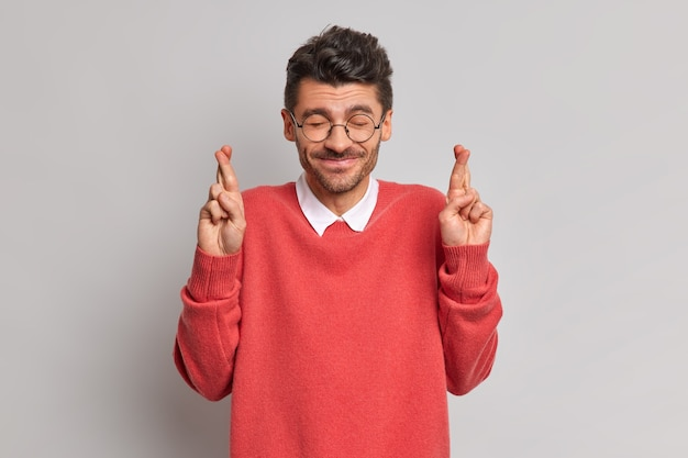Positieve gelukkige man sluit de ogen, gelooft dat dromen uitkomen hoopt op promotie op het werk kruist de vingers
