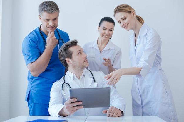 Positieve gelukkige volwassen beoefenaars die werken en digitale gadgets gebruiken in de kliniek terwijl ze genieten van een gesprek en positiviteit delen