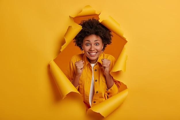 Positieve gelukkige vrouw met afro-kapsel, steekt gebalde vuisten op, glimlacht breed, vormt in gescheurde gatachtergrond