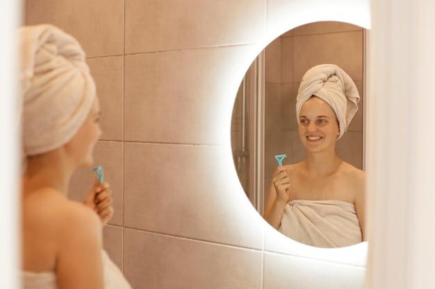 Positieve gelukkige vrouw met scheermes voor het scheren van de oksel in de hand, poseren in de badkamer voor de spiegel, hygiëneprocedures doen met een goed humeur en glimlach.