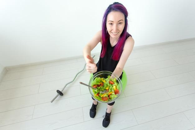 Positieve gemengd ras hipster meisje met gekleurd haar een lichte griekse salade eten na fysieke training op een witte muur. het concept van goede voeding en gewichtsverlies.