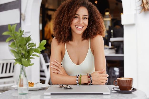 Positieve gemengd ras vrouw met donkere huid en stralende glimlach, geniet van koffiepauze, zit tegen café interieur.