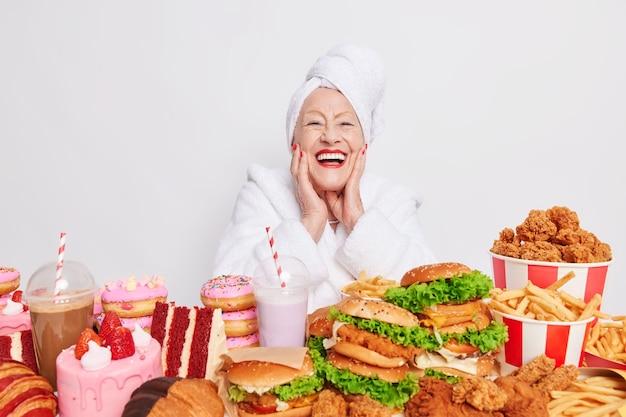 Positieve gerimpelde volwassen vrouw houdt hand op wangen glimlacht breed heeft perfecte, zelfs witte tanden, rode nagels en lippen