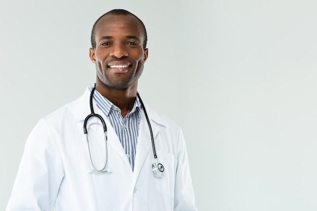 Positieve glimlachende afro amerikaanse arts die zich tegen witte achtergrond bevindt