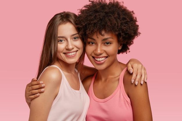 Positieve glimlachende diverse beste vrienden omhelzen elkaar, hebben vriendschappelijke relaties, poseren voor een gemeenschappelijke foto, blij om elkaar te ontmoeten, geïsoleerd over roze muur. interraciale vriendschap, ondersteuningsconcept