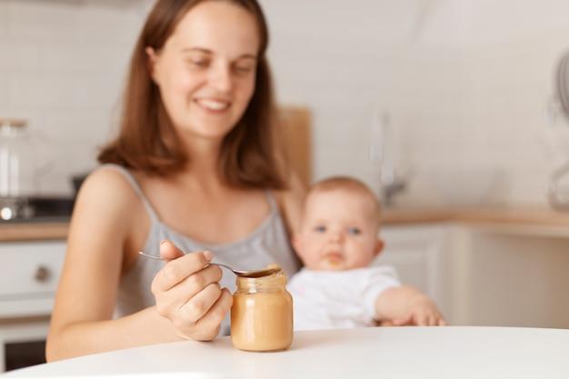 Positieve glimlachende jonge volwassen donkerharige moeder die haar dochtertje voedt met fruit- of groentepuree, lepel vasthoudt met gezond voedsel, poserend in de keuken.