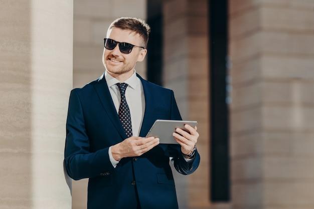 Positieve glimlachende man met stoppels, draagt zonnebril en zwart pak, houdt moderne touchpad