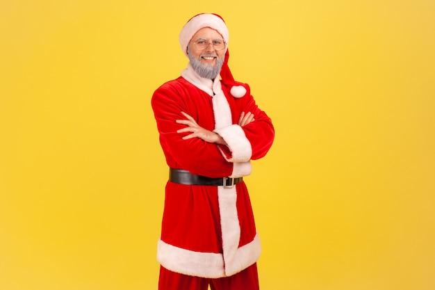 Positieve glimlachende oudere man met grijze baard in kerstmankostuum die direct naar de camera kijkt, handen gevouwen, gelukkige zelfverzekerde uitdrukking. indoor studio opname geïsoleerd op gele achtergrond.