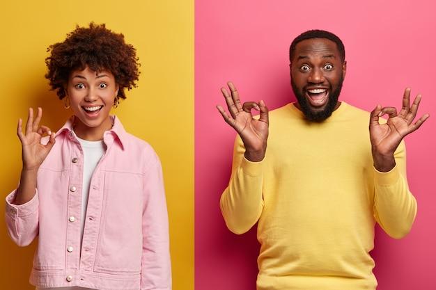 Positieve glimlachende vrouw en man met een donkere huidskleur tonen goede gebaren met tevreden assertieve uitdrukkingen, promoten een item of bevelen een koopproduct aan, geven uitstekende feedback, beoordelen iets geweldigs