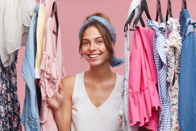 Positieve glimlachende vrouw, gekleed in wit t-shirt en sjaal, kijkend door kledingstang terwijl ze in haar paskamer staat, blij met veel nieuwe modieuze kleding. mode en mensen concept