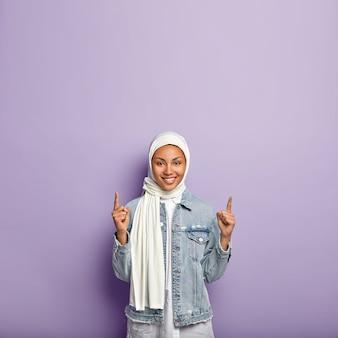 Positieve, goed uitziende moslimvrouw wijst naar boven, reageert op geweldige promo-kopie ruimte