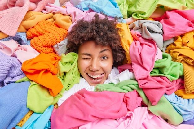 Positieve grappige afro-amerikaanse vrouw omringd door kleurrijke gebruikte kleding verzameld voor recycling of donatie reinigt haar kledingkast houdt het hoofd door stapel veelkleurige kledingstukken toont tong