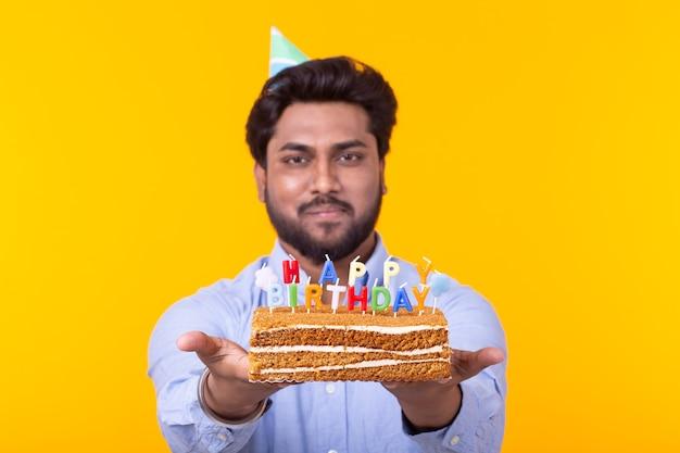 Positieve grappige jonge aziatische man met een pet en een brandende kaars en een cake in zijn handen die zich voordeed op een gele ruimte. verjaardag en verjaardag concept. advertentie ruimte