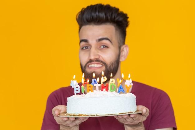 Positieve grappige jonge kerel met een pet en een brandende kaars en een zelfgemaakte cake in zijn handen die zich voordeed