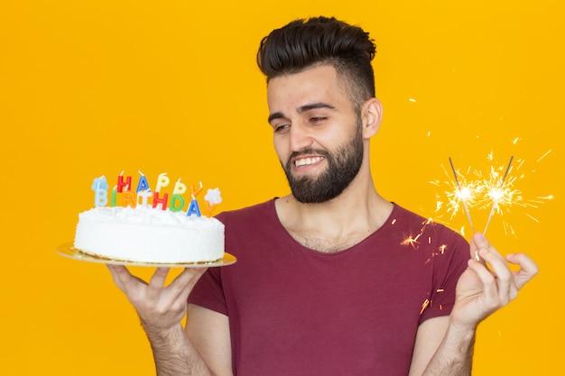 Positieve grappige jonge kerel met een pet en een brandende kaars en een zelfgemaakte cake in zijn handen poseren op een gele achtergrond. verjaardag en verjaardag concept.