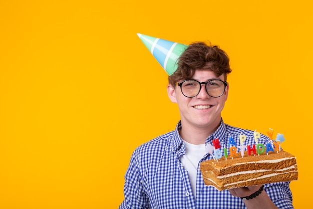 Positieve grappige jonge kerel met een pet en een zelfgemaakte cake in zijn handen die zich voordeed op een gele muur