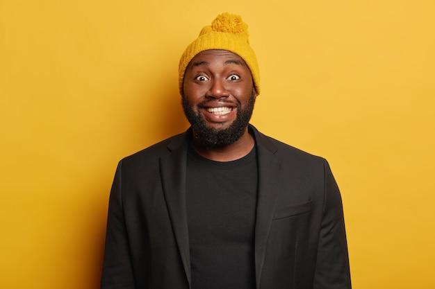Positieve grappige jongere met een zwarte huid, heeft een stralende, aantrekkelijke glimlach, toont witte tanden, lacht vrolijk, gekleed in formele kleding en warme gebreide muts staat binnen