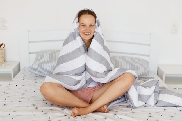 Positieve grappige lachende vrouw zittend op bed in lichte slaapkamer gewikkeld in grijs en wit gestreepte deken, camera kijken, plezier vroeg in de ochtend wakker worden.