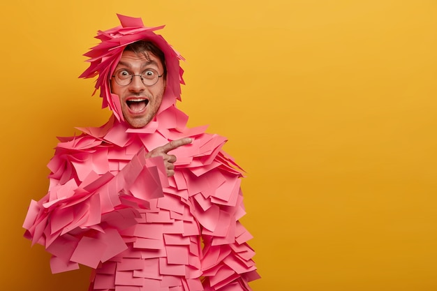 Positieve grappige man wijst op een lege ruimte in de rechterbovenhoek, maakt reclame voor een product, draagt outfit gemaakt van zelfklevende briefjes, ronde bril, geïsoleerd over gele muur. kijk hiernaar