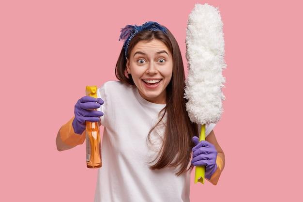 Positieve huishoudster of huishoudster houdt wasmiddel en borstel vast, draagt vrijetijdskleding, reinigt stof, gebruikt reiniger, ziet er positief uit