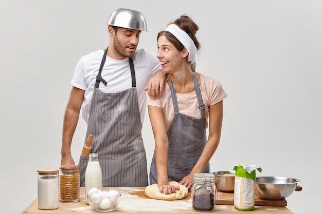 Positieve huisvrouw geeft culinaire masterclass voor echtgenoot, laat zien hoe je deeg maakt en kneedt, samen ontbijt klaarmaakt in een gezellig huis, koekjes maakt, schorten draagt, vrije tijd in de keuken doorbrengt.