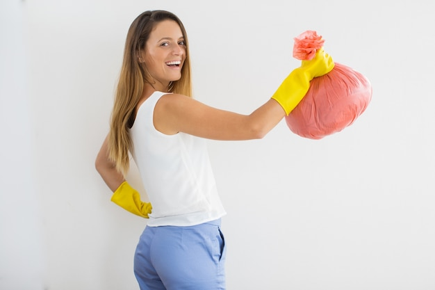 Positieve huisvrouw in rubberhandschoenen met vuilniszak