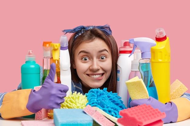 Positieve huisvrouw met blije uitdrukking, houdt duim omhoog, tevreden met goed werk in huis, gebruikt schoonmaakproducten, zorgt voor netheid