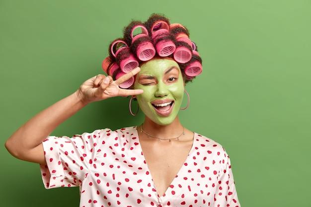 Positieve huisvrouw vindt het leuk om tijd te besteden aan het zorgen voor zichzelf vormen v teken knipoogt oog heeft vrolijke uitdrukking past effectief groen gezichtsmasker maakt kapsel draagt polka dot kamerjas
