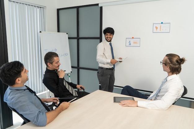 Positieve indiase man die jaarverslag presenteert op personeelsvergadering.