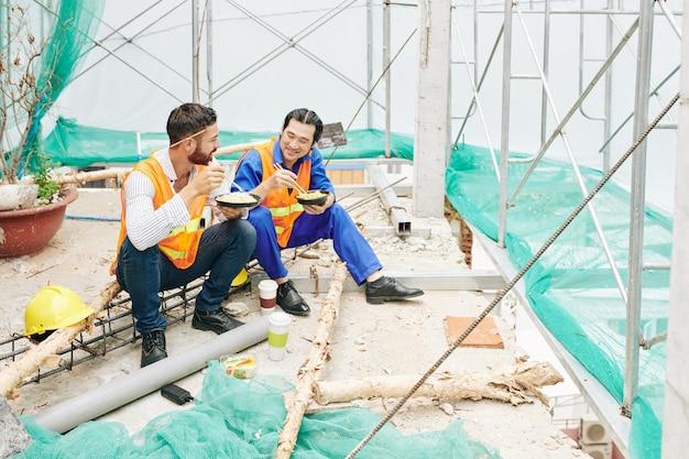 Positieve ingenieur en aannemer die lunchen op de bouwplaats, noedels eten en nieuws en werk bespreken