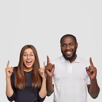 Positieve interraciale vriend gaat wat lekkers pakken in cafetaria, laten zien waar ze heen gaan, met wijsvingers naar boven aangeven